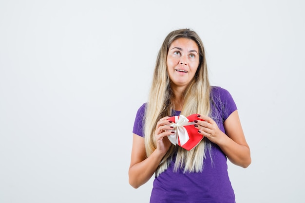 Junge dame im violetten t-shirt hält geschenkbox und schaut fröhlich, vorderansicht.