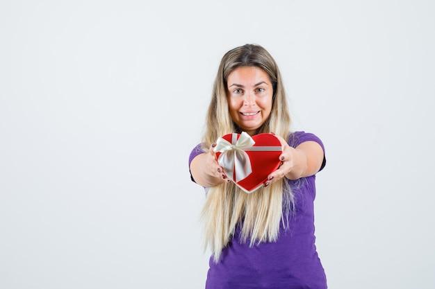 Junge dame im violetten t-shirt zeigt geschenkbox und schaut glücklich, vorderansicht.