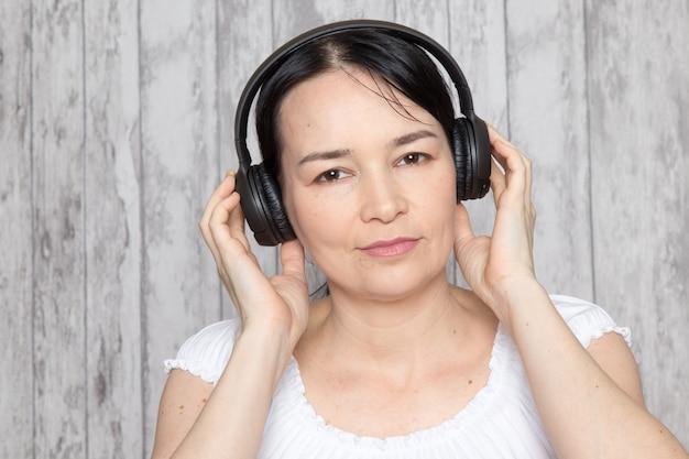 Junge dame im weißen hemd, das musik in schwarzen kopfhörern auf grauer wand hört