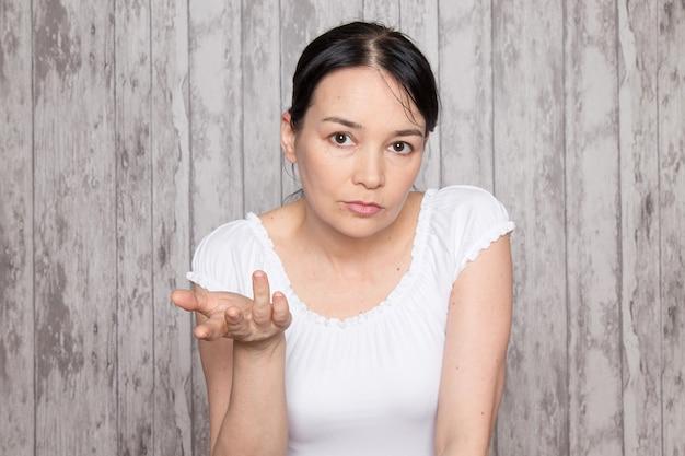 Junge dame im weißen hemd emotionen hände erhoben auf graue wand