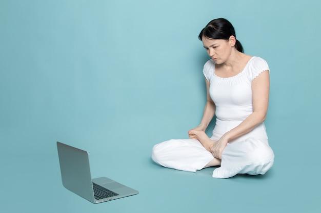 Junge dame im weißen hemd weiße hose, die mit grauem laptop auf blau schaut
