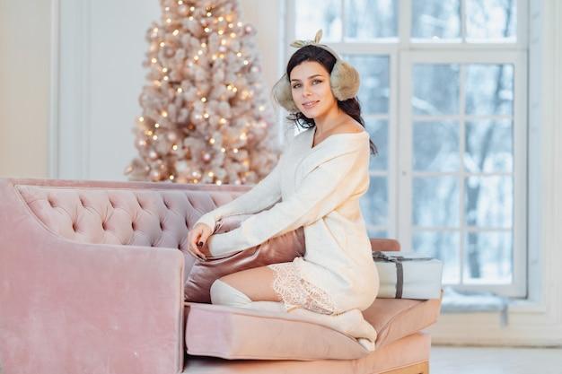 Junge dame im weißen kleid auf dem sofa in der weihnachtszeit