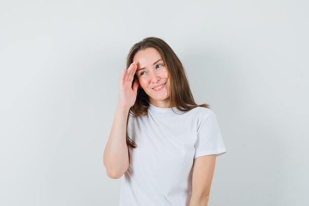 Junge dame im weißen t-shirt, das hinter der hand beiseite schaut und beschämt schaut