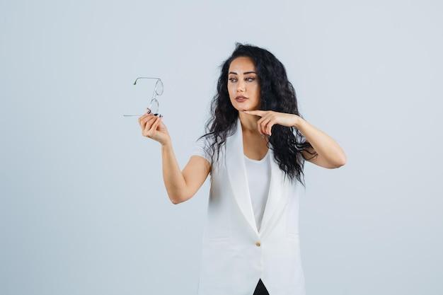 Junge dame im weißen t-shirt, jacke, die auf die brille zeigt und selbstbewusst aussieht, vorderansicht.