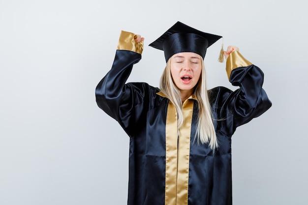 Junge dame in akademischer kleidung, die aggressiv die hände hält und vergesslich aussieht