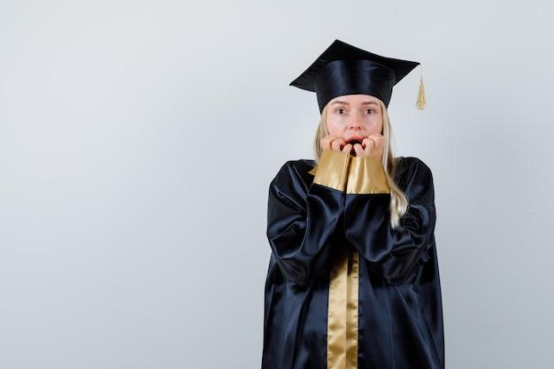 Junge dame in akademischer kleidung, die die hände auf den mund hält und verängstigt aussieht