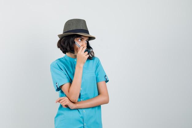 Junge dame in blauem hemd, hut, brille, die beiseite schaut, während sie ihre brille abnimmt und verblüfft aussieht.