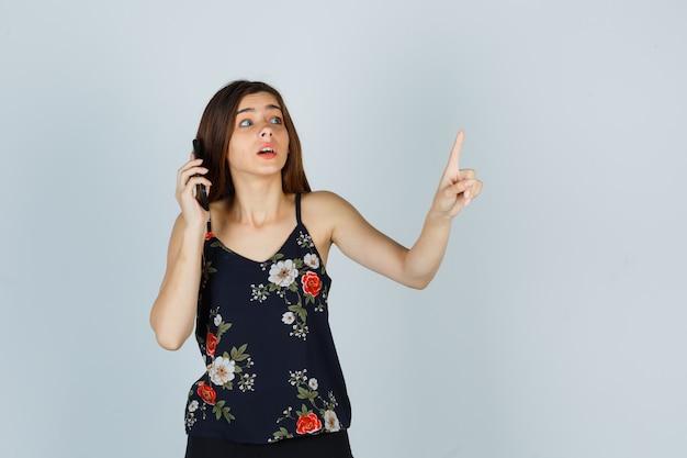 Junge dame in bluse, die eine winzige geste zeigt, während sie auf dem smartphone spricht und vorsichtig aussieht, vorderansicht.