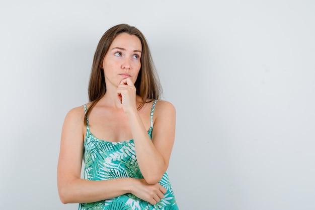 Junge dame in bluse, die in denkender pose steht und nachdenklich aussieht, vorderansicht.