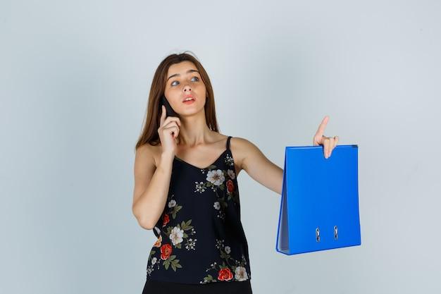 Junge dame in bluse, die ordner hält, mit dem handy spricht, eine winzige geste zeigt und vorsichtig aussieht, vorderansicht.