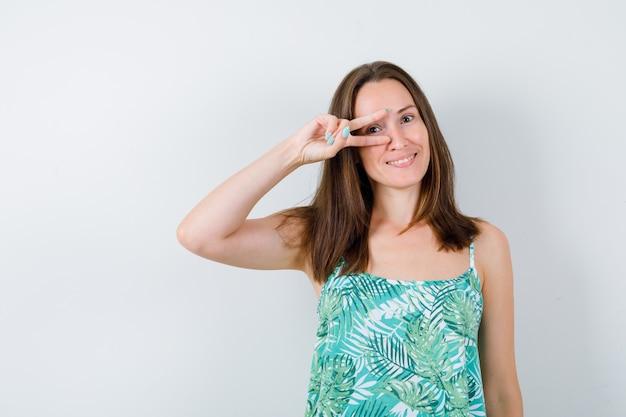Junge dame in bluse, die victory-zeichen zeigt und glückselig aussieht, vorderansicht.