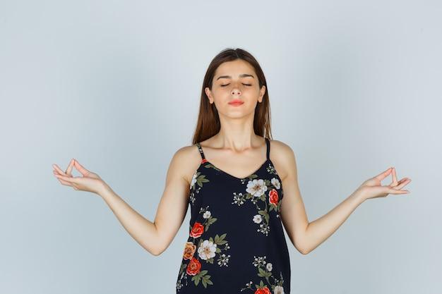 Junge dame in bluse, die yoga-geste mit geschlossenen augen zeigt und hoffnungsvoll aussieht, vorderansicht.