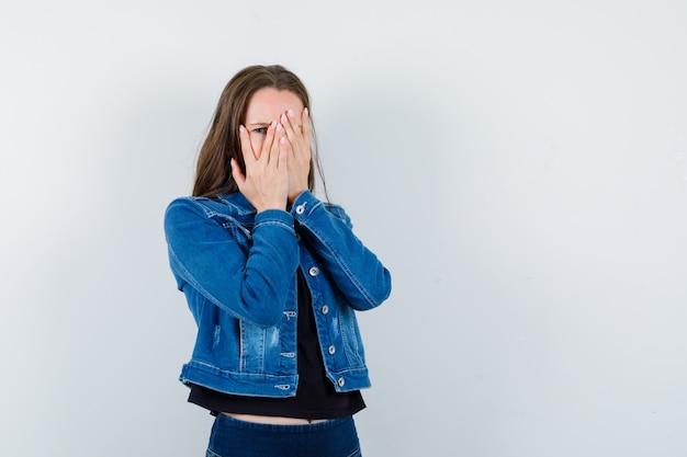 Junge dame in bluse, jacke, die durch die finger schaut und verängstigt aussieht, vorderansicht.