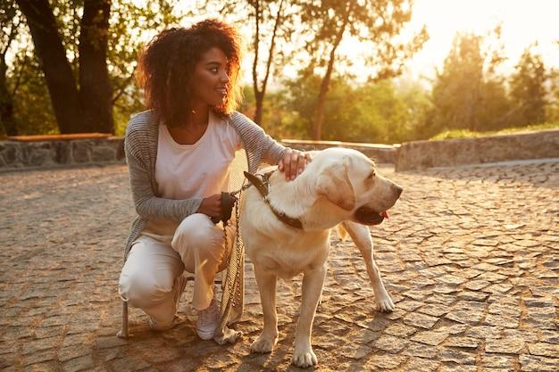 Junge dame in der freizeitkleidung, die hund im park sitzt und umarmt