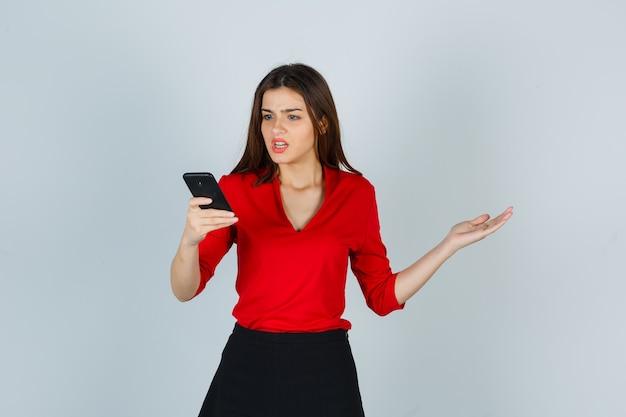 Junge dame in der roten bluse, rock, der handy betrachtet
