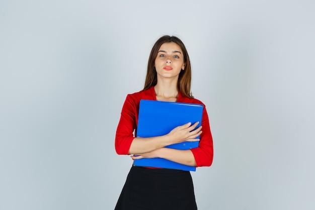Junge dame in der roten bluse, rock, der ordner auf brust hält und selbstbewusst aussieht