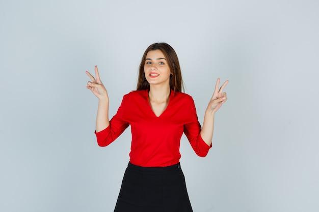 Junge dame in der roten bluse, rock, der siegeszeichen zeigt und glückselig aussieht