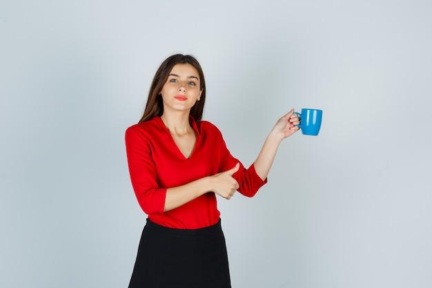 Junge dame in der roten bluse, rock, der tasse hält, während daumen oben zeigt und zuversichtlich schaut