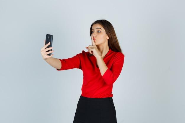 Junge dame in der roten bluse, rock, der videoanruf macht, während schweigegeste zeigt