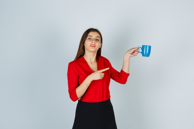 Junge dame in der roten bluse, rock zeigt auf tasse, während sie posiert und selbstbewusst aussieht