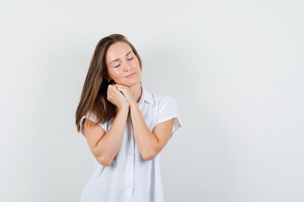 Junge dame in der weißen bluse, die ihre augen schließt, während kissen geste macht und schläfrig aussieht