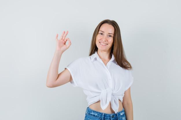 Junge dame in der weißen bluse, die ok geste zeigt und froh schaut, vorderansicht.