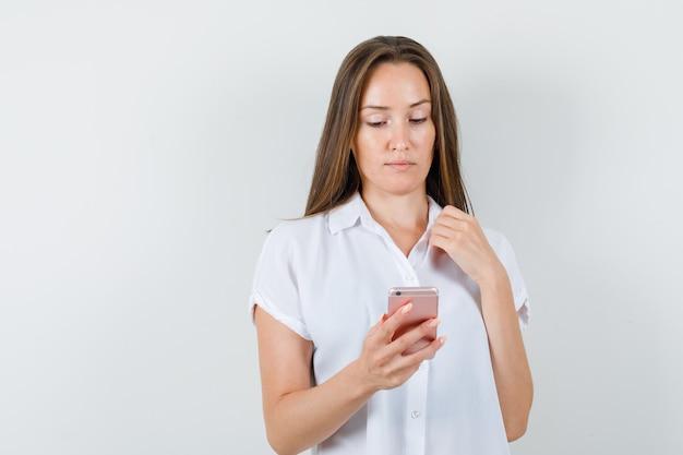 Junge dame in der weißen bluse, die telefon betrachtet und konzentriert schaut