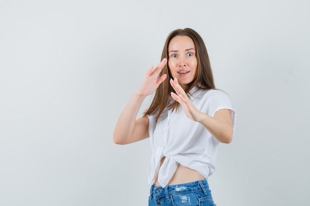Junge dame in der weißen bluse, die vorbeugend arme hebt und fokussierte vorderansicht schaut.