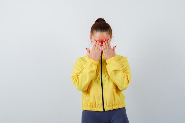 Junge dame in gelber jacke, die das gesicht mit den händen bedeckt und deprimiert aussieht, vorderansicht.
