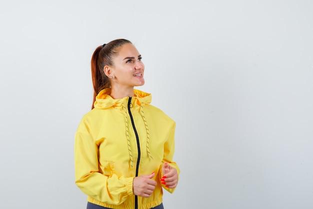 Junge dame in gelber jacke, die posiert, während sie beiseite schaut und fröhlich aussieht, vorderansicht.