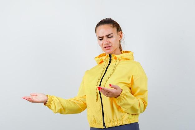 Junge dame in gelber jacke, die sich an ihren handflächen öffnet und unzufrieden aussieht, vorderansicht.