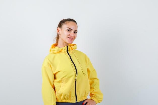 Junge dame in gelber jacke posiert und sieht zufrieden aus, vorderansicht.