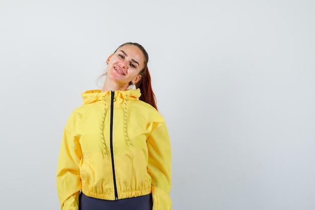 Junge dame in gelber jacke posiert, während sie fröhlich aussieht, vorderansicht.