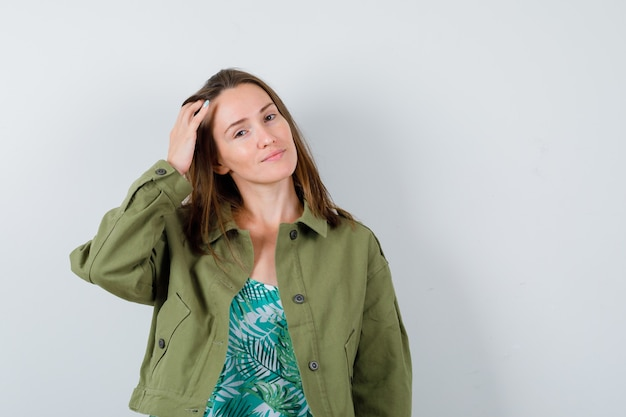 Junge dame in grüner jacke, die mit der hand auf dem kopf posiert und verführerisch aussieht, vorderansicht.