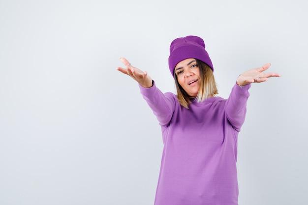 Junge dame in lila pullover, mütze, die arme zum umarmen öffnet und fröhlich aussieht, vorderansicht.