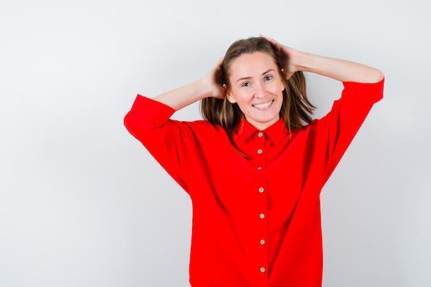 Junge dame in roter bluse, die die hände auf den kopf hält und glücklich aussieht, vorderansicht.