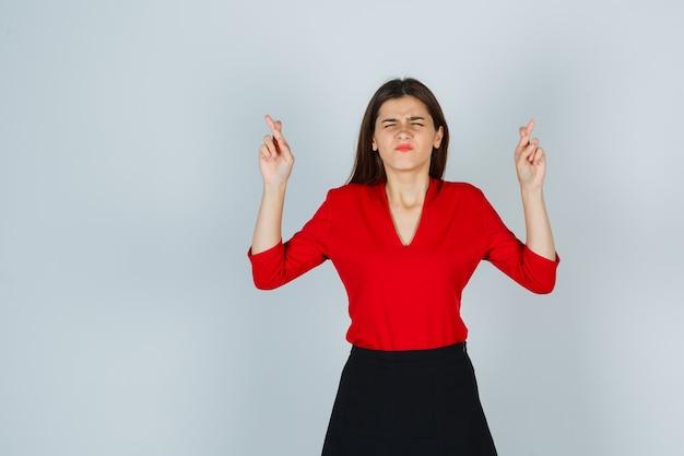 Junge dame in roter bluse, rock, der augen schließt, während gekreuzte finger zeigen