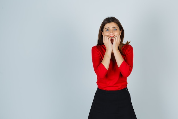 Junge dame in roter bluse, rock, der in ängstlicher haltung steht und erschrocken aussieht