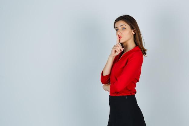 Junge dame in roter bluse, rock, der stille geste zeigt und ernst aussieht