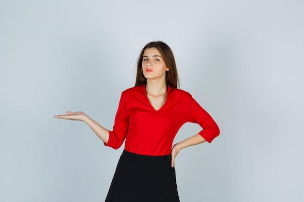 Junge dame in roter bluse, rock, der vorgibt, etwas zu halten, während hand auf hüfte gehalten wird