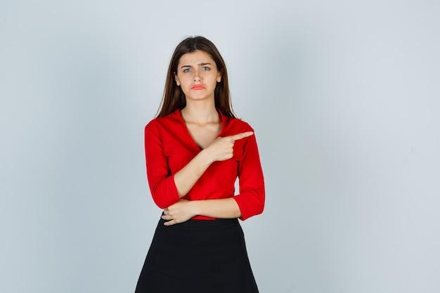 Junge dame in roter bluse, rock zeigt nach rechts und sieht wehmütig aus