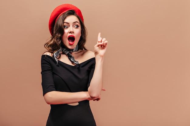 Junge dame in schwarzem kleid, roter mütze und schal dachte an neue idee und zeigt mit dem zeigefinger nach oben.
