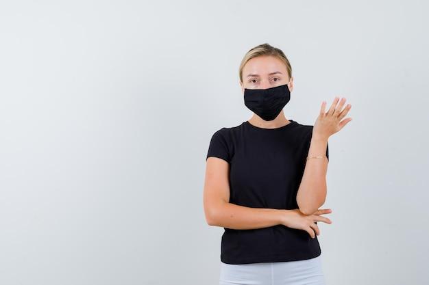 Junge dame in t-shirt, hose, medizinische maske, die die hand isoliert ausdehnt