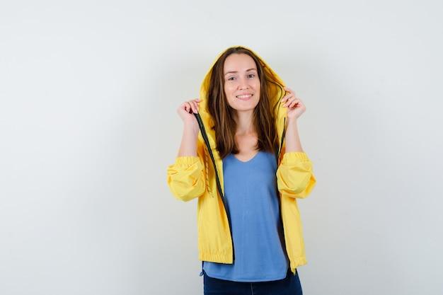 Junge dame in t-shirt, jacke posiert, während sie ihre kapuze hält und selbstbewusst aussieht, vorderansicht.