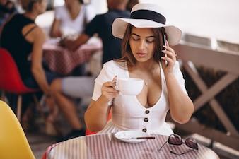 Junge Dame in trinkendem Kaffee der Bar und am Telefon sprechend