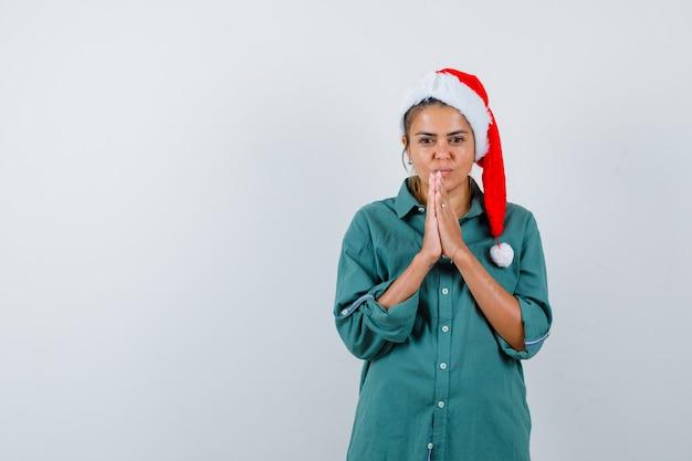 Junge dame in weihnachtsmütze, hemd mit händen in betender geste und hoffnungsvoller blick, vorderansicht.