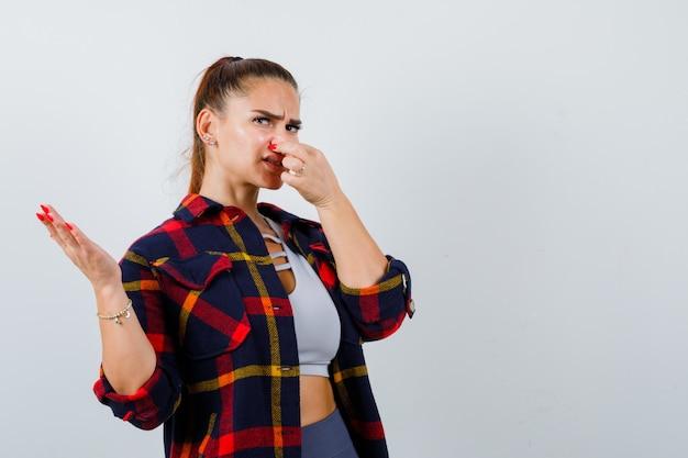 Junge dame kneift die nase aufgrund von schlechtem geruch im oberteil, kariertem hemd und sieht angewidert aus. vorderansicht.
