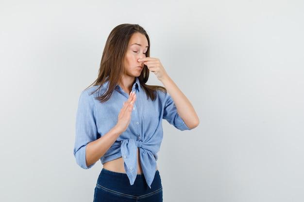 Junge dame kneift die nase wegen des schlechten geruchs in blauem hemd, hose und sieht angewidert aus