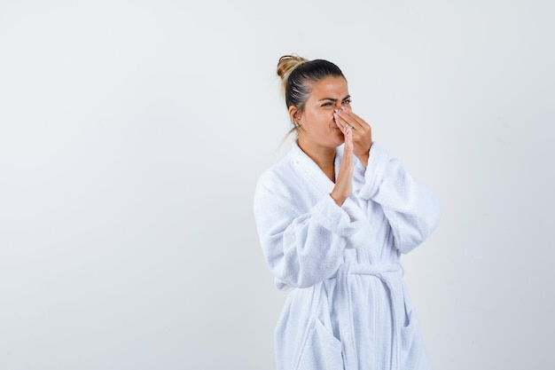 Junge dame kneift die nase wegen schlechten geruchs im bademantel und sieht angewidert aus