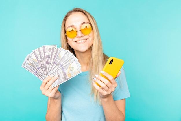 Junge dame lokalisiert über blauem hintergrund. schauende kamera, die anzeige des handys zeigt, das geld hält.